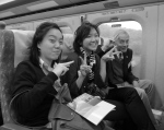 On the high-speed train from Taichung back to Taipei, SAISers Katie Wei-ruo Xiao and Charlotte Chiang flash peace signs (or victory signs as they're sometimes called in Asia) with Professor Brown.  Photo by Jingbo Jing.